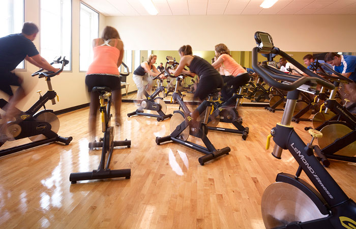 Men and women cycling during a Magnuson Athletic Club group fitness class.